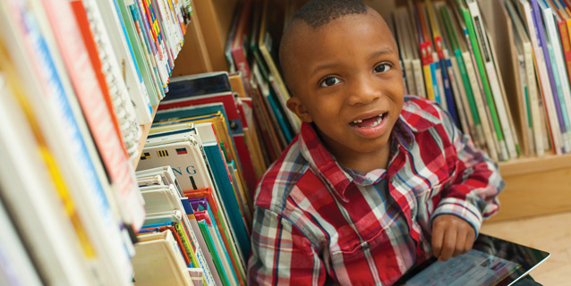 Little boy in library looking at computer tablet.