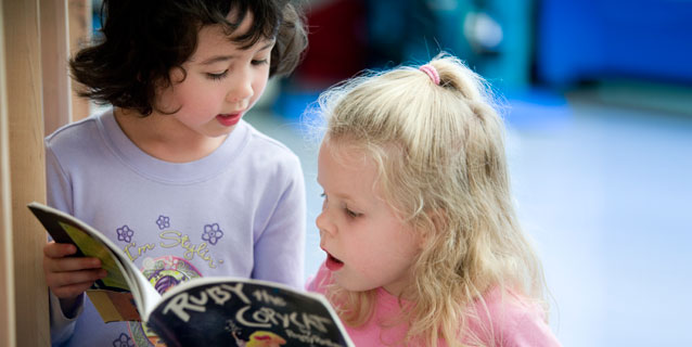 Two little girls reading a book.