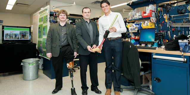 Three men in a lab. One with prosthetic knee and two scientists.