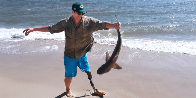 Man with prosthetic leg on the beach holding a fish.