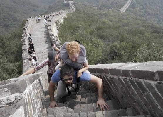 Man being carried in backpack by another man on the Great Wall of China