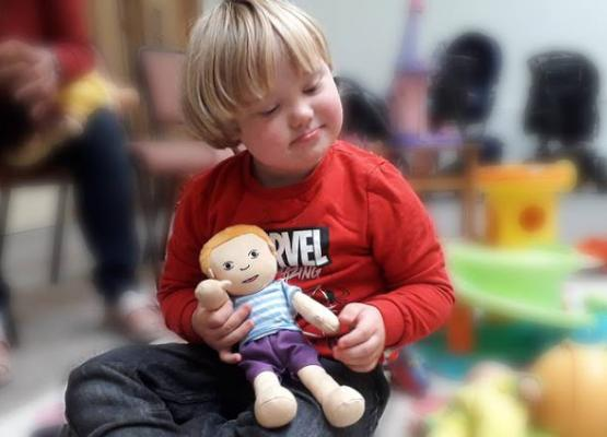 Little boy holding soft doll.