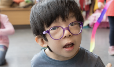 Young boy with glasses and dark hair looking at the camera