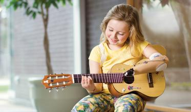 Girl with a prosthetic arm playing a guitar