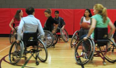Five youth in wheelchairs playing basketball