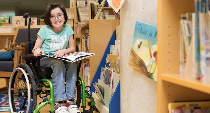Girl with dark hair and glasses in a wheelchair reading a book.
