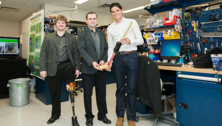 A young man with a prosthetic leg standing next to a scientist