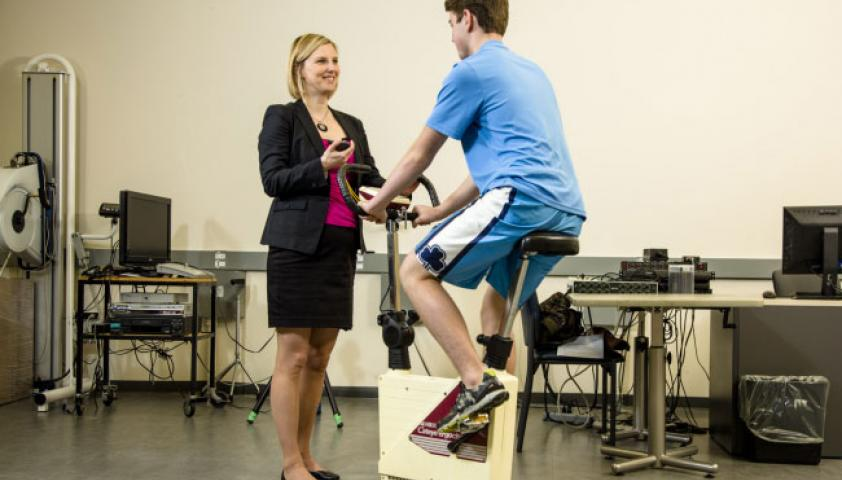 Scientist with a participant on an exercise bike