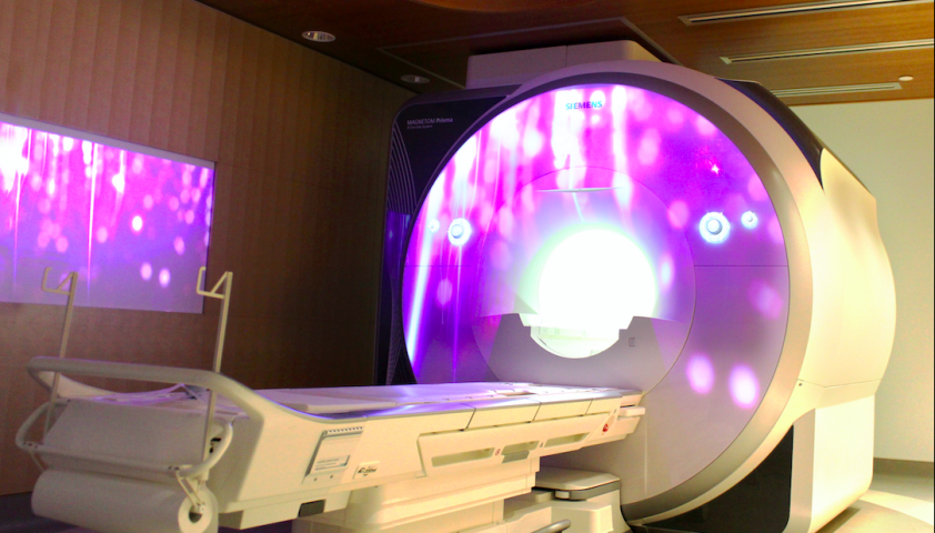 Photo of the MRI with a purple projection on it.